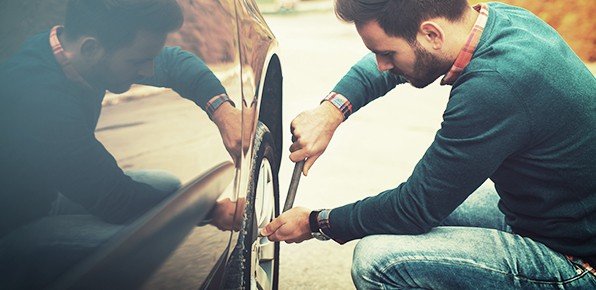 Male-Driver-Removing-Hubcap-From-Tire